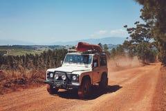 皮船在乡下公路的被装载的SUV 免版税库存图片