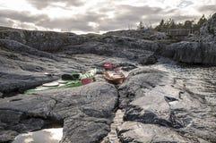 皮船在岩石岸站立停泊,在那里背景中是 库存照片