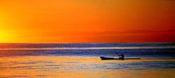 皮船在日落的海洋 库存图片