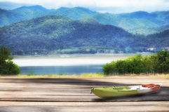 皮船小船和木板条与山使看法背景环境美化 免版税图库摄影