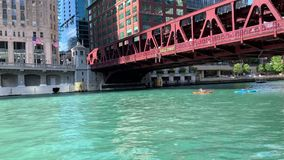 皮船横渡在芝加哥河的富兰克林街被举起的'el'火车桥梁下 股票录像