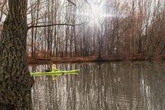 皮船的一个女孩 在河的女孩浮游物皮船的 免版税库存图片