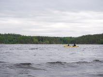 皮船的人们在湖 库存图片