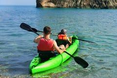 皮船 在有山的海岛附近结合kanoeing在海 皮船 库存图片