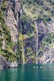 皮艇享用风景和瀑布Milford Sound,一新西兰` s多数普遍的旅游目的地 免版税库存图片