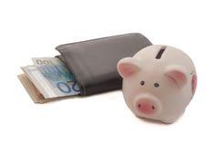 黑皮革两褶的钱包和存钱罐 免版税库存照片