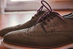 皮革人的有色的鞋带的方鞋子在与后面轻的特写镜头的地板上 免版税库存图片