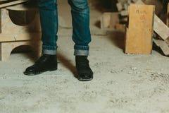黑皮革人` s穿上鞋子时髦和经典牛仔裤 免版税库存照片