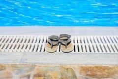 皮革凉鞋是在游泳池边缘 免版税库存照片