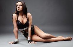 黑皮革女用贴身内衣裤的性感的拉丁舞蹈家在灰色背景 库存照片