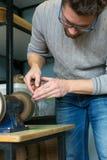 皮革工匠削尖切开的皮革刀子在沙磨机 r 创造皮革的小企业的概念 免版税库存照片