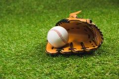 皮革棒球手套和球在绿草 库存照片