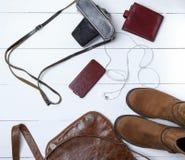 皮革棕色起动,在案件与耳机,钱包的智能手机 免版税库存照片