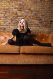 皮革沙发的时尚女孩 免版税库存照片