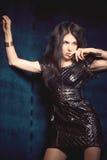 黑皮革礼服的女孩在蓝色天鹅绒背景  免版税库存照片