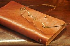 皮革笔记本和玻璃在木背景 库存图片