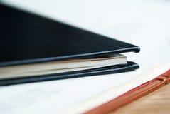 黑皮革笔记本在有白色板料的一个开放笔记本说谎 库存照片