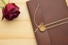 皮革笔记本在木背景上把放的盖子和英国兰开斯特家族族徽 免版税图库摄影