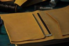 皮革车间黄色皮革和工具在桌上 库存图片