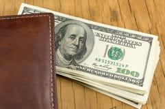皮革钱包和掉下来的美金 免版税库存图片