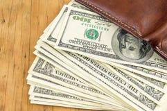 皮革钱包和掉下来的美金 免版税图库摄影