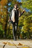 皮革长裤的美丽的女孩通过秋天公园漫步 免版税库存图片