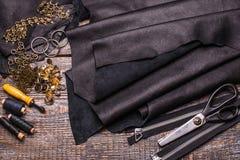 皮革,缝合的一个集合板料缝合的皮革事的在木背景 免版税库存照片