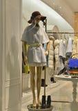 皮靴和一个女性时装模特穿戴褐色盖帽在时尚商店窗口里 免版税库存图片