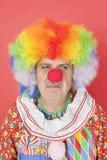 皱眉在红色背景的资深男性小丑 免版税库存图片