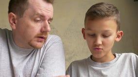 皱眉头父亲和儿子饶恕,谈论某事在书桌 影视素材