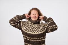 皱眉温暖的棕色的毛线衣的年轻女性塞住她的耳朵和她的懊恼与噪声的面孔 库存图片