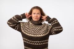 皱眉温暖的棕色的毛线衣的年轻女性塞住她的耳朵和她的懊恼与噪声的面孔 库存照片