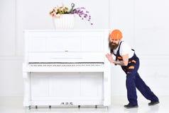 皱眉的搬家工人,当移动重的钢琴时 调迁在公寓的疲乏的人材料在白色背景 家 图库摄影