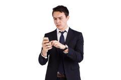 皱眉年轻白种人的商人看手机 库存照片