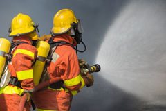 盆射在消防的2名消防队员水与黑暗的烟b 免版税库存照片