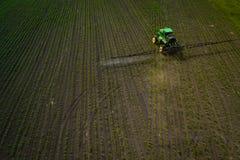 盆射领域的拖拉机与化学制品在春天 免版税库存照片