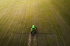盆射领域的拖拉机与化学制品在春天 库存照片