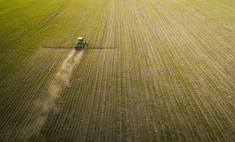 盆射领域的拖拉机与化学制品在春天 库存图片