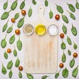 盐、胡椒混合物和在菠菜叶子和西红柿附近被计划的一个白色葡萄酒切板的橄榄油, 免版税库存照片