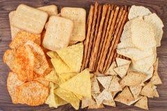 盐味的油炸马铃薯片、面包棒和曲奇饼,不健康的食物的概念堆  免版税库存图片