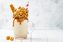 盐味的焦糖纵容极端奶昔用brezel奶蛋烘饼、玉米花和打好的奶油 疯狂的freakshake食物趋向 图库摄影