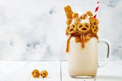 盐味的焦糖纵容exreme奶昔用brezel奶蛋烘饼、玉米花和打好的奶油,疯狂的freakshake食物趋向 复制空间 免版税图库摄影