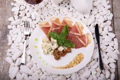 盐味的熏火腿或balyk,坚果,在白色石背景的青纹干酪顶视图  消耗大的食物 企业咖啡杯方便问题午餐开张了 库存照片