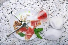 盐味的熏火腿顶视图或balyk、坚果、青纹干酪和一杯在白色石背景的酒 消耗大 免版税图库摄影