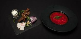 盐味的猪油用胡椒和黑面包在板材说谎,在它旁边那里镀与红色罗宋汤 特写镜头,顶视图 免版税库存照片