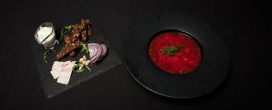 盐味的猪油用胡椒和黑面包在板材说谎,在它旁边那里镀与红色罗宋汤 特写镜头,顶视图 库存图片