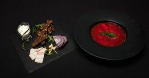 盐味的猪油用胡椒和黑面包在板材说谎,在它旁边那里镀与红色罗宋汤 特写镜头,顶视图 库存照片