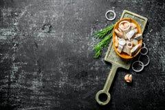 盐味的鲱鱼片断在一个切板的用莳萝、葱和大蒜 免版税图库摄影