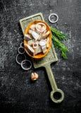 盐味的鲱鱼片断在一个切板的用莳萝、葱和大蒜 免版税库存照片