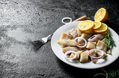 盐味的鲱鱼片断在一块板材的用切的柠檬和葱 免版税库存照片
